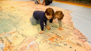 Students peer into Ethiopia on a giant floor map of Africa. (Photo by Trent Campbell)